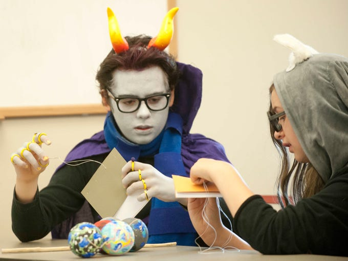 At a bookbinding class as the downtown Louisville Free Public Library, Silas Zoeller, 15, of Middletown, left, and Ella, his sister, right, learn the art of bookbinding, one of the classes at Animecon, a convention celebrating the Japanese action cartoon art form of anime. 01 Aug 2014