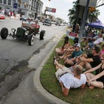 People sit in the median watching cars go by on Woodward Avenue at Nine Mile in Ferndale during the 2016 Woodward Dream Cruise on Saturday, August 20, 2016.