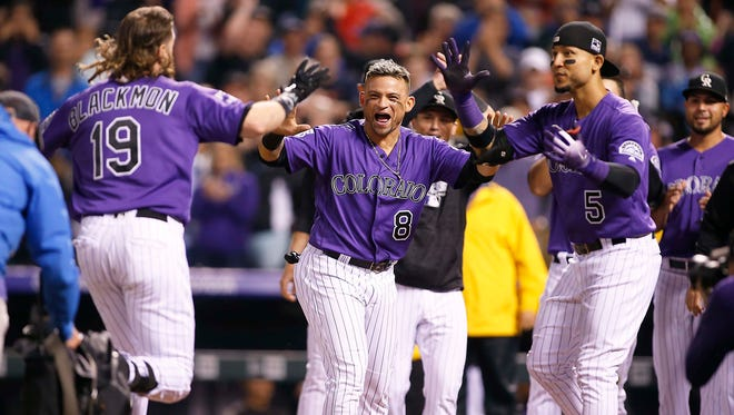 Gerardo Parra (8) and his Colorado Rockies teammates celebrate Wednesday night after Charlie Blackmon (19) hit a walk-off home run in the bottom of the ninth inning to beat the Houston Astros. The Rockies are at home this weekend for games against the Oakland Athletics.