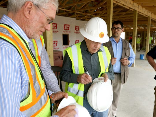 Former president Jimmy Carter signs a hard hat for