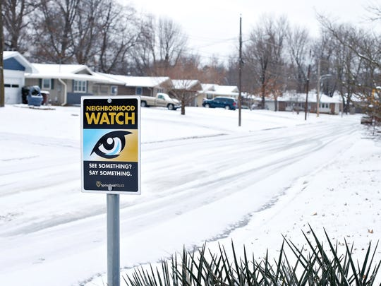A Neighborhood Watch sign stands at the entrance of South Karla Avenue, near the scene of an alleged burglary stopped by the watch last December on East Loren Street in Springfield, Mo.