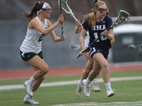 Caroline McKee, of IHA, controls the ball against Jamie Graff (2) and the Ramapo defenese, Thursday, April 12, 2018.  IHA went on to win the game, 13-4.