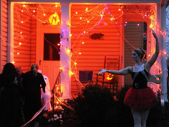 A woman dressed as a wind-up doll greets trick-or-treaters