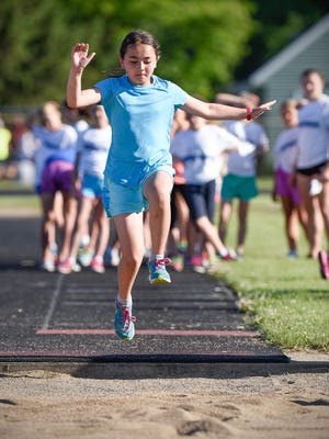 Sophie Wieland, 9, of Sartell, competes in the long jump during St. Cloud's first home track meet for third- though sixth-graders on June 23 at South Junior High School in St. Cloud.