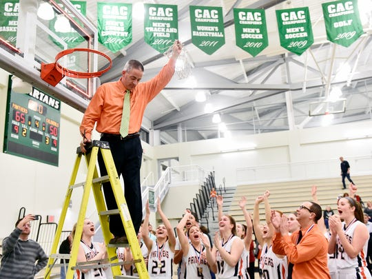 Central York head basketball coach Scott Wisner holds up the cut net to show the team after the YAIAA girls' basketball championship game Thursday, Feb. 16, 2017, at York College. Central York defeated New Oxford 65-50 to win the title.