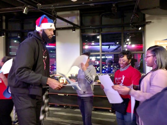 Detroit Pistons center Andre Drummond hands a $1,000 check on Sunday, Dec. 17, 2017 to Carmen Wallace, second fropm right, at a Season of Giving party team members threw for families and children at the Little Caesars Arena in Detroit.