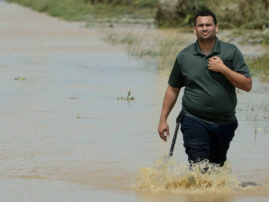A resident walks on a flooded road after the passing