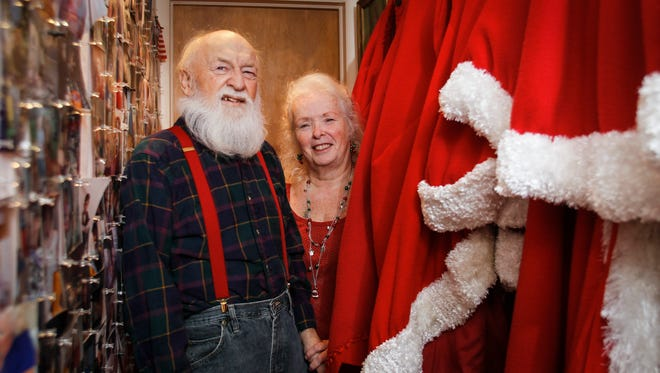 Roger and Millie Fortin of Haslett at the landing atop their stairs December 4, 2015.  The couple have been making appearances as Santa and Mrs. Claus for over a decade.  Millie made their clothing by hand.