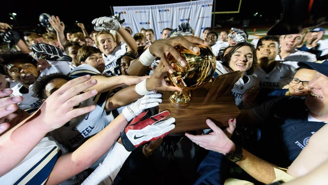 Casteel players and Casteel's head coach Spencer Stowers (right) celebrate with the AIA Div 3A championship trophy after their victory game on Saturday, Nov. 25, 2017, at Campo Verde High School in Gilbert, Ariz.