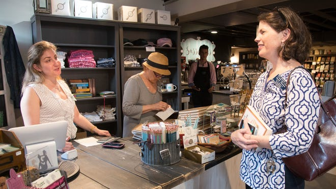 Kathleen Madden, left, asks local author Sarah Thomas, right, to sign her books for sale at Sassafras on Sutton recently.