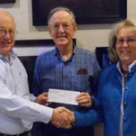 Steve Arbour, left, presents a $4,000 check to George Gault, MRB chairman, and Gaye Stockman, MRB CEO.