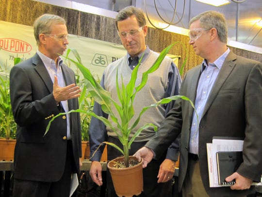 Rick Santorum, center, wears a sweater vest in December 2011. He talks with  is shown talking with Pioneer Hi-Bred executives Dennis Byron, left,and Jerry Flint, right, at the company's corn research facilities in Johnston, Iowa