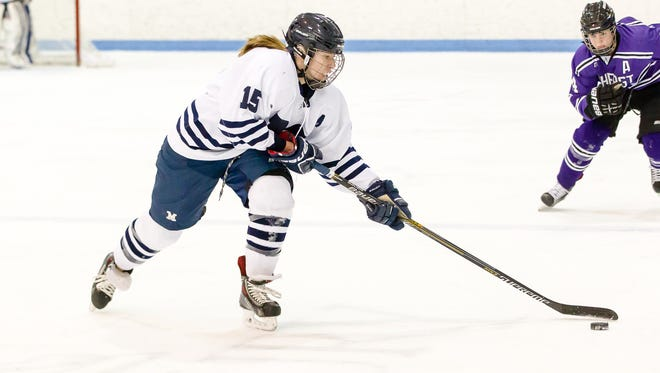 Middlebury's Katie Mandigo reaches for the puck during Sunday's NESCAC championship game at Kenyon Arena.