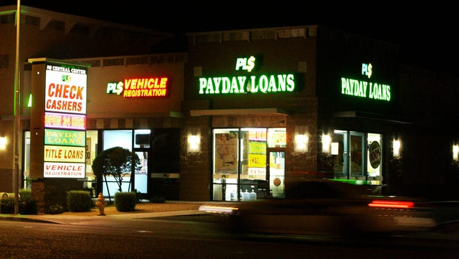 Neon signs illuminate a payday loan business. Payday loan borrowers often roll over their loans and wind up paying more in fees than they borrowed, the Consumer Financial Protection Bureau warns in a report out Tuesday.