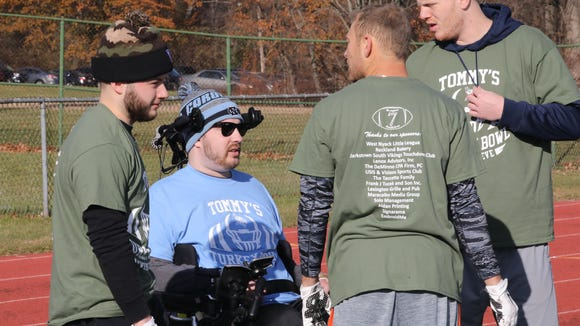 Tommy McGuire, center, paralyzed in a swimming pool accident, chats with friends on the sideline of the Clarkstown South High School football field in West Nyack, Nov. 25, 2017. The second annual Tommy McGuire Turkey Bowl was held as a fundraising event.