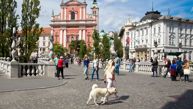 In this Friday, Aug. 12, 2016 photo, tourists and residents walk across Tromostovje bridge in downtown Ljubljana, Slovenia The tiny European nation of Slovenia is undergoing a tourism boom partly because it is the native country of U.S. first lady Melania Trump.