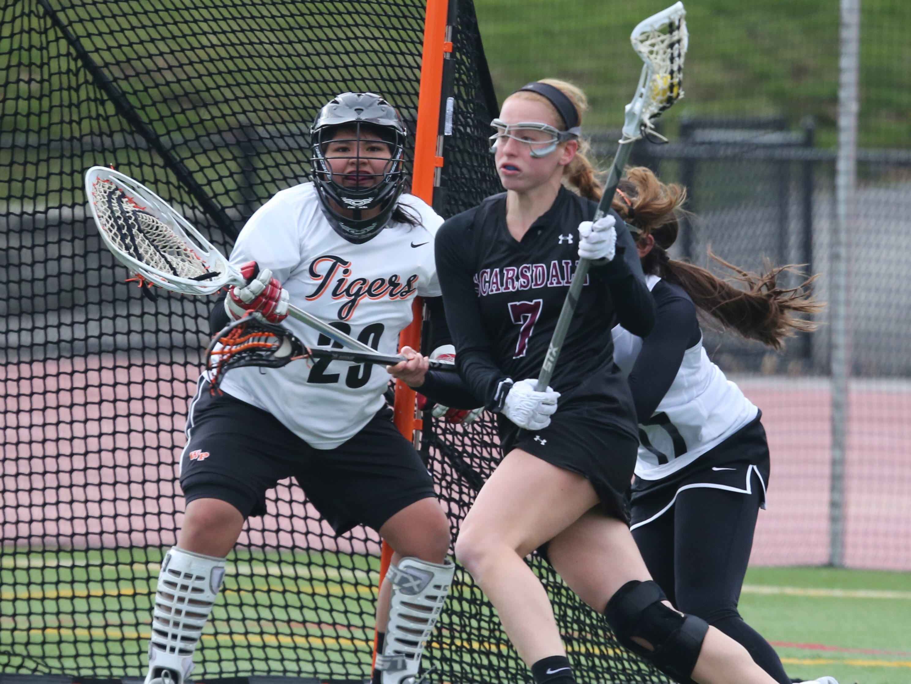 Scarsdale's Eliza Brosgol moves the ball in front of White Plains goalie Jennifer Ortega-Salazar during their girls lacrosse game at White Plains High School, April 6, 2016.