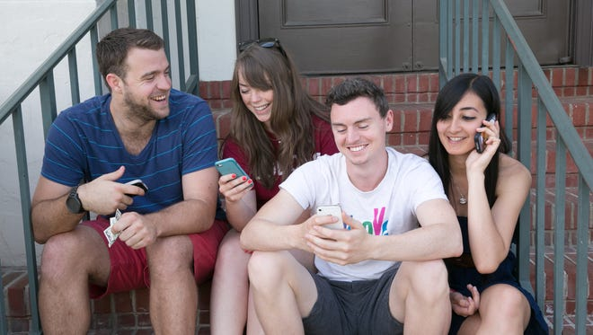 """Loyola Marymount University students on campus. Left to right: Dillon Siler, Sarah """"Bear"""" Sievers, Kevin Halladay-Glynn and Kristina Williams. Siler and Halladay-Glynn like to pay their bills via mobile apps like Venmo and banking apps. Sievers and Williams prefer their debit cards."""