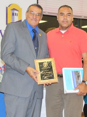 LULAC Council 8003's Fred Baca presents the LULAC Educator of the Year Award to Silver High School teacher and coach Claudie Thompson.
