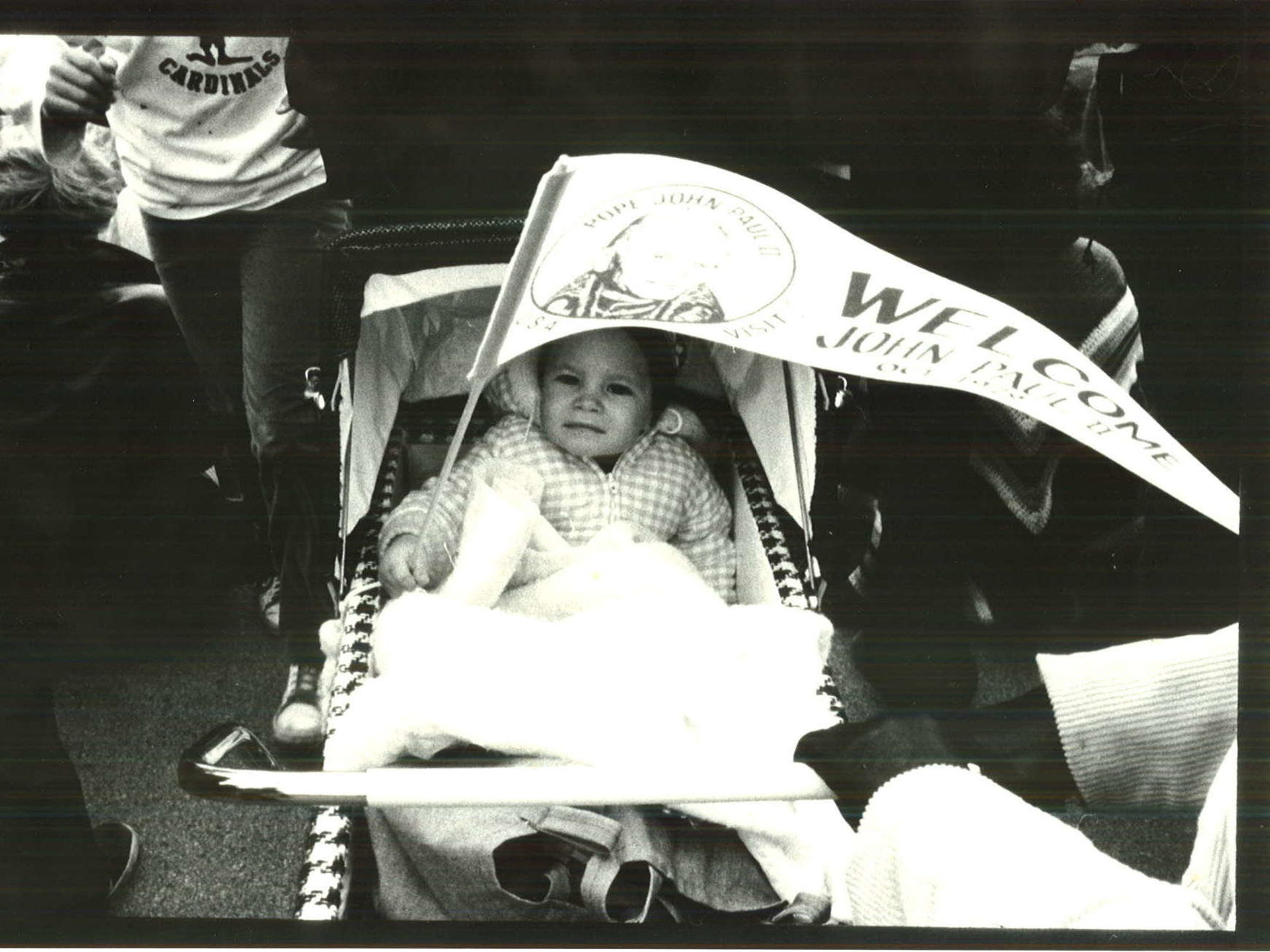 A baby keeps warm with a pennant while awaiting Pope John Paul II's arrival at Living History Farms on Oct. 4, 1979.