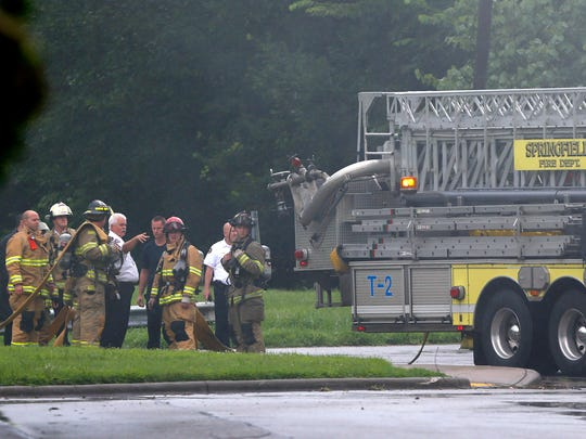 Firefighters stand behind a firetruck as they wait