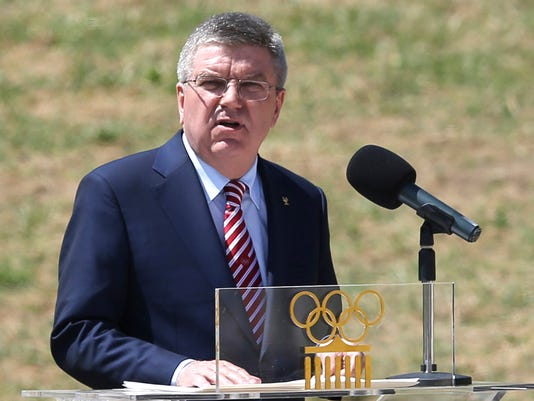 FILE- In this Thursday, April 21, 2016 file photo, IOC President Thomas Bach delivers a speech during the ceremonial lighting of the Olympic flame in Ancient Olympia, Greece. Bach says entire sports federations could be suspended if allegations of state-supported Russian doping at the 2014 Sochi Olympics are proven.  (AP Photo/Petros Giannakouris, File)