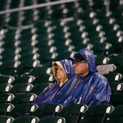 Baseball fans wait for the rain to stop during a game
