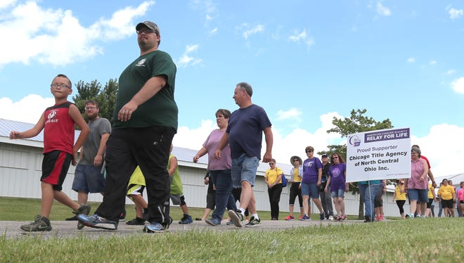 Volunteers for the Richland County Relay for Life complete the first lap at the fairgrounds on Saturday. The vent was an all day fundraiser for the American Cancer Society.