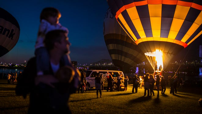 Father Karl Richter holds his son Maxwell on his shoulders at the annual Kentucky Derby Festival Balloon Glimmer event at Waterfront Park on Thursday evening. April 27, 2017