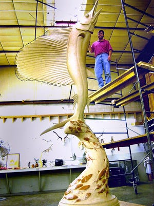 """Local artist Geoffrey Smith stands next to his sculpture """"The Stuart Sailfish"""" in Lander Wyoming in 2002."""