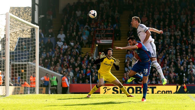 John Terry (R) of Chelsea is pressured by Joe Ledley of Crystal Palace and heads the ball over his goalkeeper, Petr Cech.