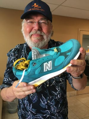 """Jan Kassies, director of visitor services for the Lake Havasu City Convention and Visitors Bureau, holds a Concepts/New Balance 991.5 """"Made in U.K."""" Lake Havasu shoe."""