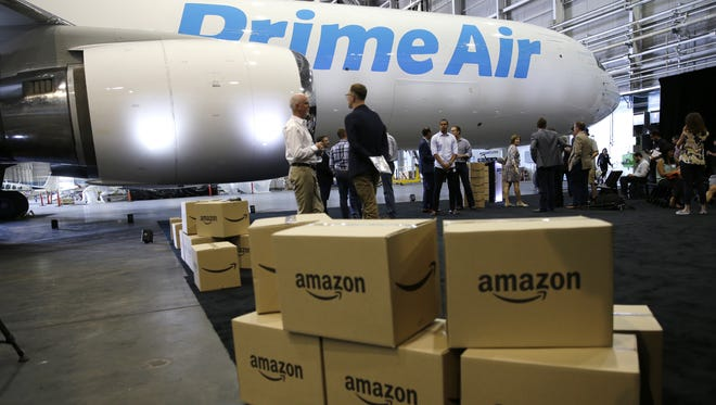 """In this Aug. 4, 2016, file photo, Amazon.com boxes are shown stacked near a Boeing 767 Amazon """"Prime Air"""" cargo plane on display in a Boeing hangar in Seattle. Amazon's announcement on Jan. 30, 2017, of a new air cargo hub in Kentucky is the latest way the e-commerce retailer is dipping its toe, or perhaps whole foot, into building out its shipping and logistics unit. If successful, the move ultimately means lower costs for Amazon but it could eventually pit Amazon against package deliverers like FedEx and UPS. (AP Photo/Ted S. Warren, File)"""