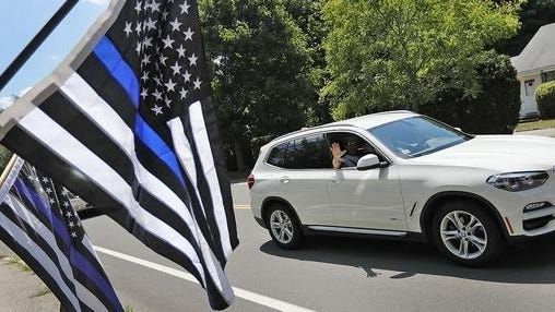 "A car passes protestors during a ""back the blue"" rally called in response to town and public safety leaders telling Hingham firefighters to remove thin blue line flags from their trucks. Greg Derr/Patriot Ledger photo."