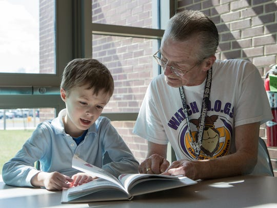 Louis Agosta, of Salisbury, reads a book with his son Skyler, 7, in the media center at Prince Street Elementary School on Monday, March 21, 2016.  Agosta is a member of the Watch D.O.G.S. program, which allows fathers to become a role model for students.