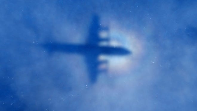 In this Monday photo, a shadow of a Royal New Zealand Air Force P-3 Orion aircraft is seen on low cloud cover while it searches for missing Malaysia Airlines Flight MH370 in the southern Indian Ocean.