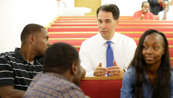 Gov. Scott Walker greets people at Greater Praise Church of God in Christ, at 5422 W. Center St. in Milwaukee  last month. The governor later announced that an additional $4.5 million in state funding would be made available for the city.