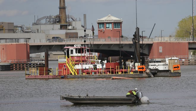 Brennan Marine employees work from a dredging barge removing PCBs from the Fox River in 2016, just south of the Ray Nitschke Memorial Bridge in downtown Green Bay.