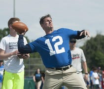 Harbaugh stood on stage and fired footballs to tho...