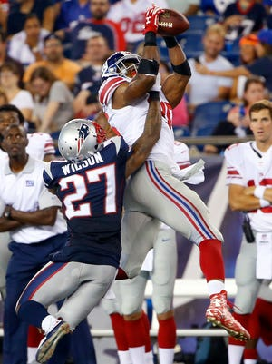 New York Giants tight end Jerome Cunningham, rear, catches a pass over New England Patriots strong safety Tavon Wilson (27) in the second half of an NFL football game Thursday, Sept. 3, 2015, in Foxborough, Mass.