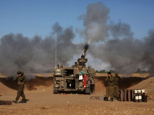 An Israeli tank near the border with Gaza fires toward targets in the Palestinian enclave on July 17.