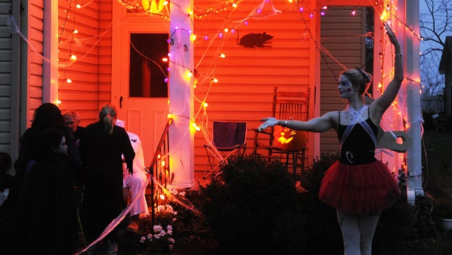 A woman dressed as a wind-up doll greets trick-or-treaters in the Sherwood neighborhood during Halloween in Staunton.