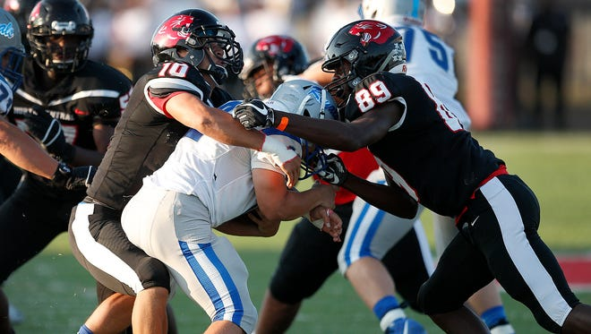North Central'sRamon Stalling,left, and Justin Helm,right, sack Hamilton Southeastern's quarterback Cody Huppenthal (12) in the first half of their game at North Central High School Friday August 25, 2017.