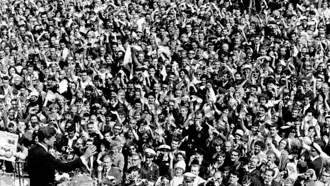 "U.S. President John F. Kennedy, left, waves to a crowd of more than 300,000 gathered to hear his speech in the main square in front of Schoeneberg City Hall in then West Berlin on June 26, 1963. In his famed ""Ich bin ein Berliner"" speech, Kennedy commends Berliners on their spirit and dedication to democracy and expresses his solidarity with them."