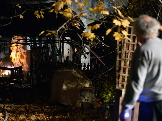 Homeowner Roger Miller, right, watches as flames consume gas from a broken line behind his home Thursday, Nov. 5, 2015, in Jefferson. Jefferson Borough Fire Department assistant chief Mark Becker said the gas meter in a utility structure behind Miller's home, which dates back to at least the 1830s, was broken and spewing gas that provided constant fuel for the flames.