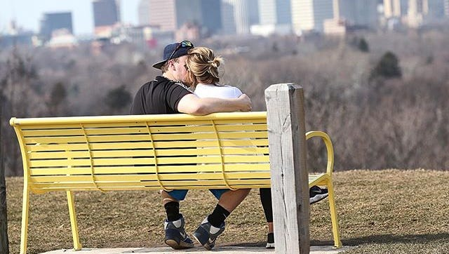 A couple sits on a bench overlooking the Rochester skyline.