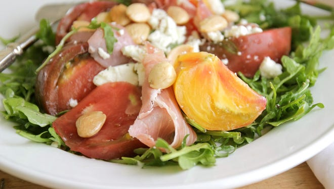 Heirloom tomatoes add color and flavor to a salad that Cru offers. It's perfect for summer.