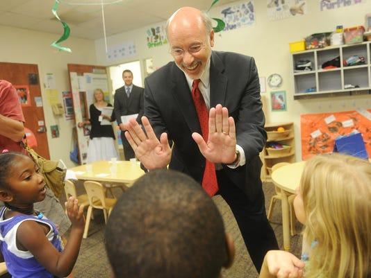 Tom Wolf, the Democratic candidate for Pennsylvania governor, high fives a group of pre-school children during a visit to York Day Nursery on Friday, Aug. 22, 2014
