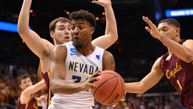 Nevada's Jordan Caroline (24) looks to pass against Loyola center Cameron Krutwig during the second half in the semifinals of the NCAA South regional last season.