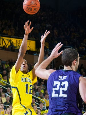 Michigan guard Muhammad-Ali Abdur-Rahkman shoots while defended by Northwestern center Alex Olah when the teams met the first time this season at Crisler Center on Jan. 17, 2015. Michigan won 56-54.